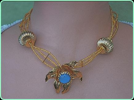 Pretty designer gold beaded three strand necklace with eye catching large gold floweer with a blue stone centre